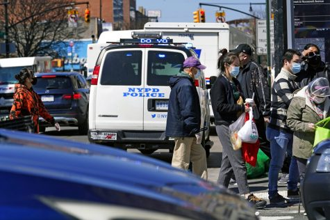 Pedestrians cross a busy intersection of Main Street in Flushing, a largely Asian American neighborhood, Tuesday, March 30, 2021, in the Queens borough of New York. Police have stepped up patrols in similar neighborhoods across the city in the wake of Monday