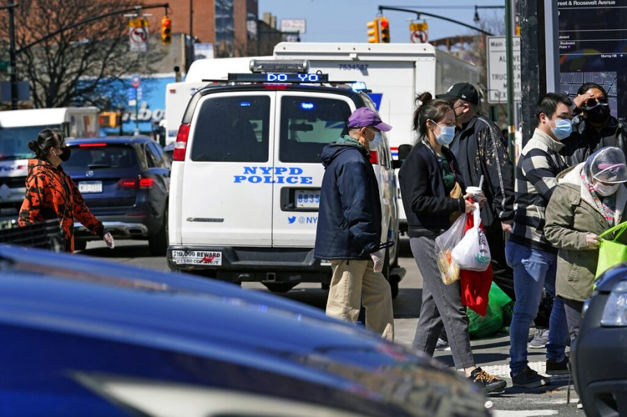 Pedestrians cross a busy intersection of Main Street in Flushing, a largely Asian American neighborhood, Tuesday, March 30, 2021, in the Queens borough of New York. Police have stepped up patrols in similar neighborhoods across the city in the wake of Monday's vicious attack on an Asian American woman during which no bystanders intervened to help. There has also been a rash of anti-Asian violence across the U.S., recently, including a deadly mass shooting in the Atlanta area that left multiple people dead, most of them of Asian descent. (AP Photo/Kathy Willens)