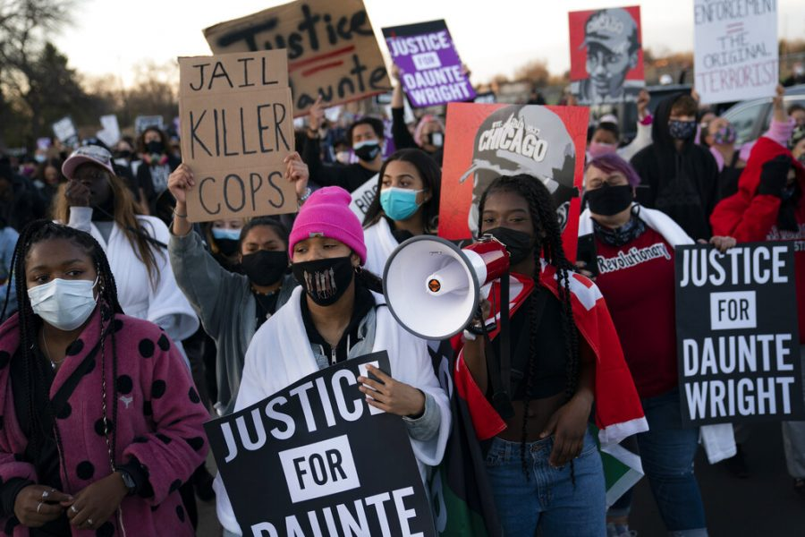 Demonstrators march during a protest over the fatal shooting of Daunte Wright during a traffic stop, outside the Brooklyn Center Police Department, Friday, April 16, 2021, in Brooklyn Center, Minn. (AP Photo/John Minchillo)