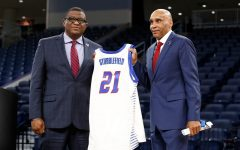 DePaul athletic director DeWayne Peevy hands Tony Stubblefield a No. 21 Blue Demon jersey.