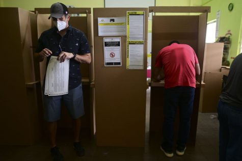 Voters use booths to mark their ballots for the general election at a polling center set up at the Rafael Labra School in San Juan, Puerto Rico, Tuesday, Nov. 3, 2020. (AP Photo/Carlos Giusti)