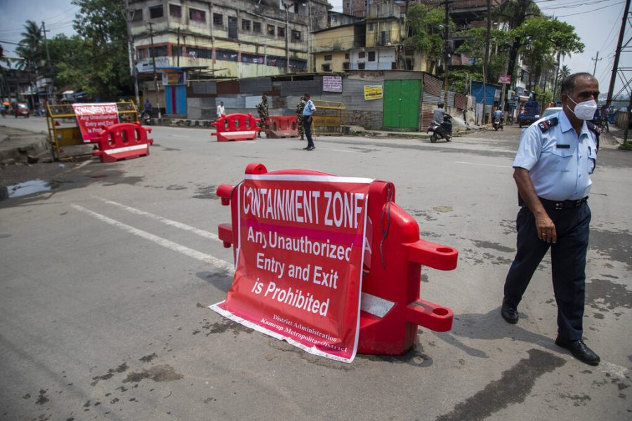 A police officer walks past a barricade displaying a signage informing about the restrictions in a containment zone in Gauhati, India, Saturday, May 8, 2021. Two southern states in India became the latest to declare lockdowns, as coronavirus cases surge at breakneck speed across the country and pressure mounts on Prime Minister Narendra Modi's government to implement a nationwide shutdown. (AP Photo/Anupam Nath)