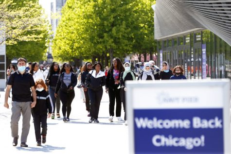People walk along Chicagos Navy Pier, Friday, May 14, 2021. The U.S. Centers for Disease Control and Prevention eased its guidelines, saying fully vaccinated people can resume activities without wearing masks. (AP Photo/Shafkat Anowar)