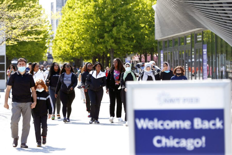 People walk along Chicago's Navy Pier, Friday, May 14, 2021. The U.S. Centers for Disease Control and Prevention eased its guidelines, saying fully vaccinated people can resume activities without wearing masks. (AP Photo/Shafkat Anowar)