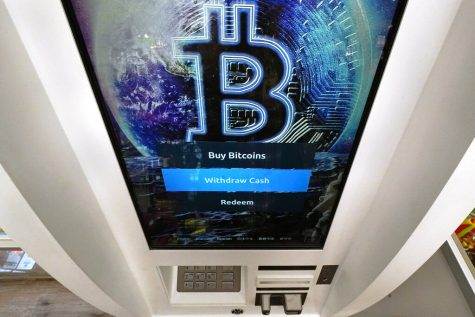 FILE - In this Feb. 9, 2021 file photo, the Bitcoin logo appears on the display screen of a crypto currency ATM at the Smoker
