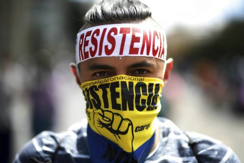 """A man wearing the word """"Resistance"""" takes part in anti-government march in Bogota, Colombia, Wednesday, May 19, 2021. Colombians have taken to the streets for weeks across the country after the government proposed tax increases on public services, fuel, wages and pensions. (AP Photo/Ivan Valencia)"""