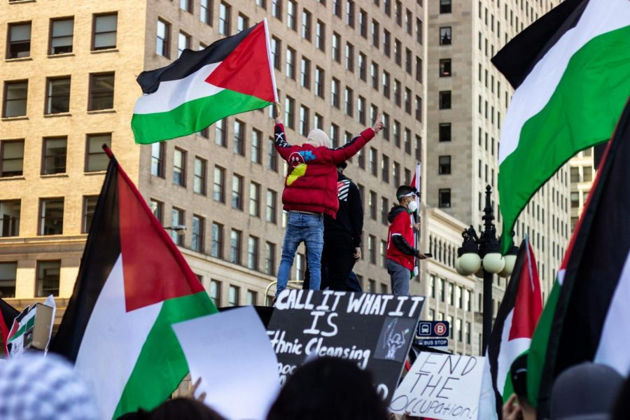FILE-Protestors+wave+the+Palestinian+flag+while+standing+on+top+of+a+bus+stop.