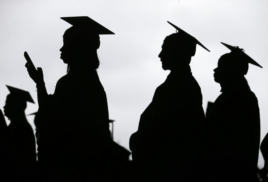 FILE - In this May 17, 2018, file photo, new graduates line up before the start of the Bergen Community College commencement at MetLife Stadium in East Rutherford, N.J.  There's no single policy or action that will alleviate America's $1.74 trillion student loan debt crisis while simultaneously preventing students from taking on unaffordable amounts of future debt. Higher education financing experts are divided on the exact combination of solutions, but all agree it will require a multipronged approach.  (AP Photo/Seth Wenig, File)