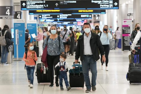 Henry Hernandez, his wife Karina Gonzalez and their children Jose Sebastian, 2, and Laura, 6, of Colombia, walk towards the baggage claim area at Miami International Airport, Friday, May 28, 2021, in Miami. The couple were surprised to be offered the Johnson & Johnson COVID-19 vaccine upon arrival to the U.S. It is their first overseas trip since the pandemic began last year. Florida