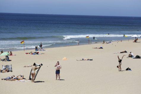 People sunbathe at Carcavelos beach near Cascais, outside Lisbon, Friday, June 4, 2021. Britain said Thursday that it is removing Portugal from its list of COVID-safe travel destinations, meaning thousands of U.K. residents currently on vacation there face the prospect of 10 days