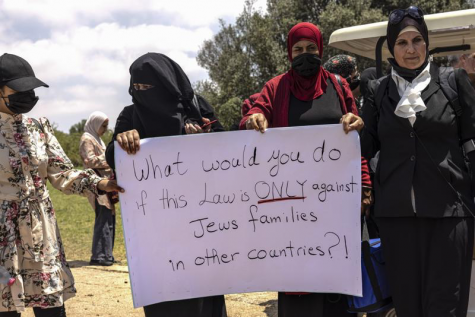 Israeli Arab women hold a sign during a protest ahead of a vote by Israel