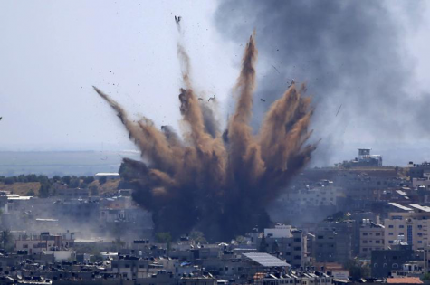 """In this May 13, 2021, file photo, smoke rises following Israeli airstrikes on a building in Gaza City. Human Rights Watch on Tuesday, July 27, 2021, accused the Israeli military of carrying attacks that """"apparently amount to war crimes"""" during an 11-day war against the Hamas militant group in May. (AP Photo/Hatem Moussa, File)"""
