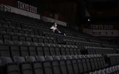 A man, wearing a protective face mask, sits inside an empty Ariake Arena, just before the start of a women's volleyball preliminary round pool A match between Japan and South Korea, at the 2020 Summer Olympics, Saturday, July 31, 2021, in Tokyo, Japan. (AP Photo/Manu Fernandez)