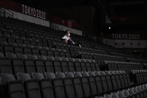A man, wearing a protective face mask, sits inside an empty Ariake Arena, just before the start of a women