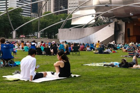 A couple sits on a picnic blanket on the Great Lawn near Pritzker Pavillion in Millenium Park to listen to Prelude to the Afternoon of a Faun performed by the Grant Park Orchestra on July 28, 2021.