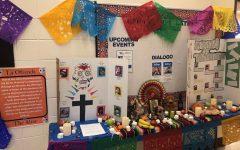 El Centro Cultural Latinx celebra el Día de los Muertos en el 2018 en persona con frutas, fotos, velas y calaveras.