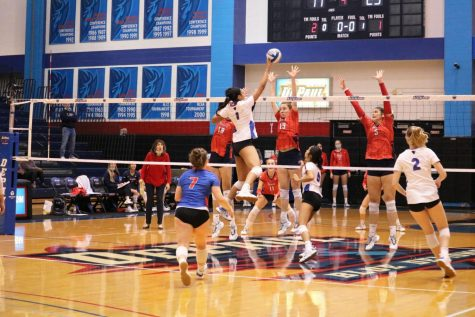 DePaul middle blocker Donna Brown tipping the ball over St. Johns blockers on Saturday.