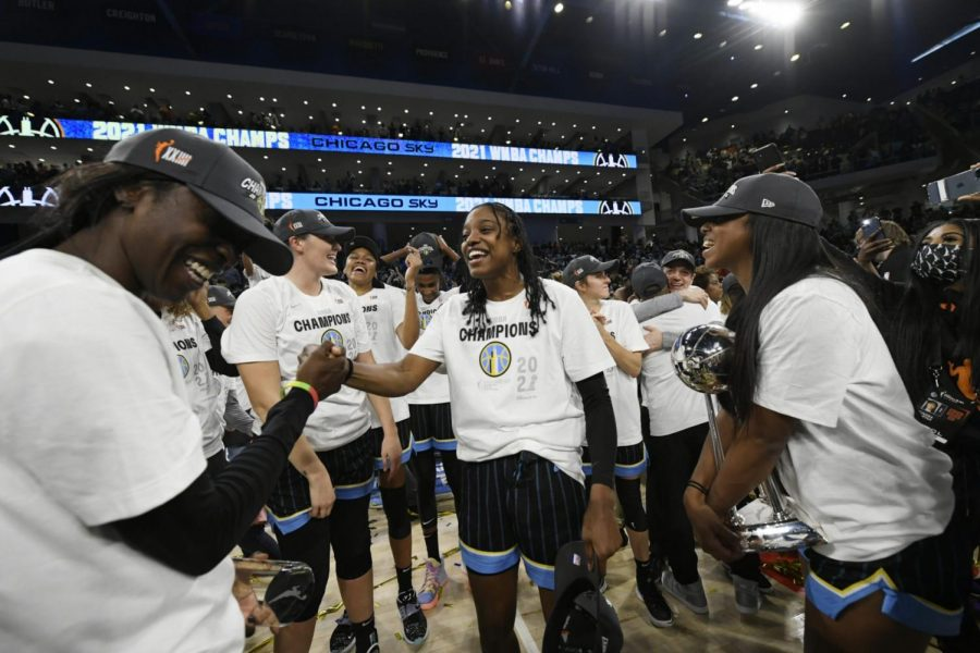 Chicago Skys Diamond DeShields, center, and Kahleah Copper left, along with teammates celebrate after defeating the Phoenix Mercury in Game 4 of the WNBA Finals to become champions Sunday, Oct. 17, 2021, in Chicago. (AP Photo/Paul Beaty)