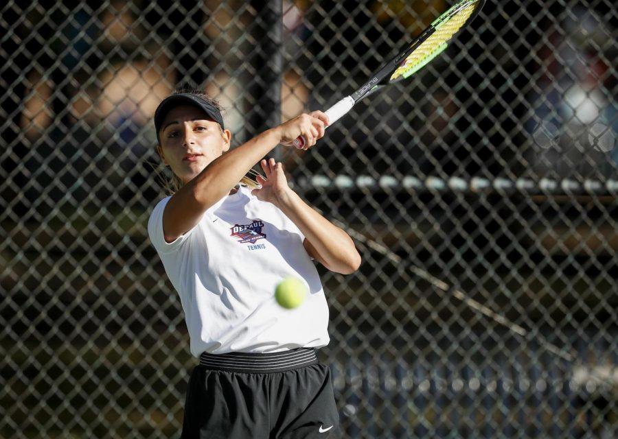 Lenka Antonijevic following through on a swing that sent a tennis ball soaring.   Photo credit: Steve Woltmann/DePaul Athletics.
